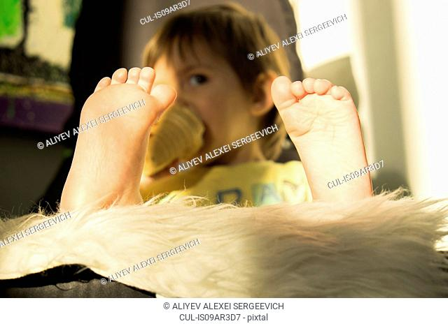 Young boy drinking from beaker, focus on feet