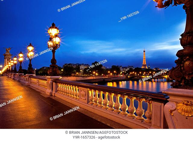 Lamps along Pont Alexandre III over River Seine with Eiffel tower beyond, Paris France