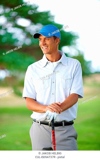 Golfer wearing golf glove and baseball cap holding golf club looking away smiling