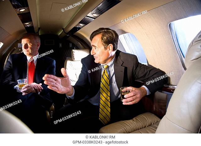 Businessmen with drinks on private jet plane