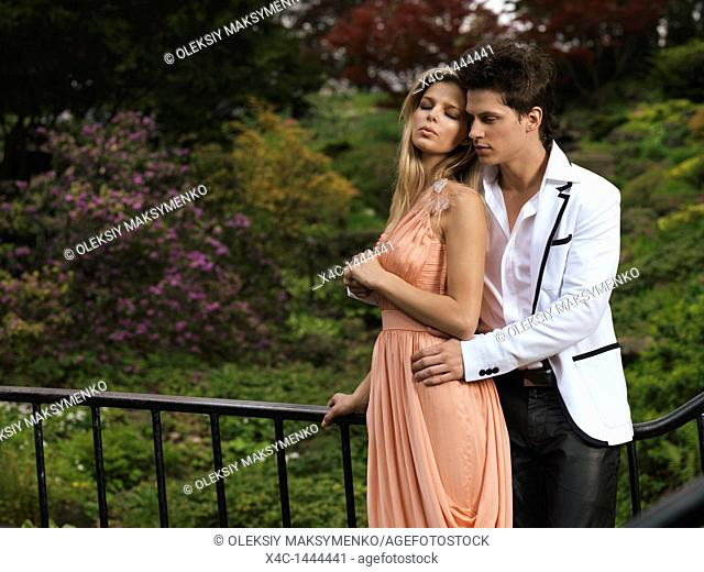 Young romantic couple standing on a bridge in a park  Springtime scenic