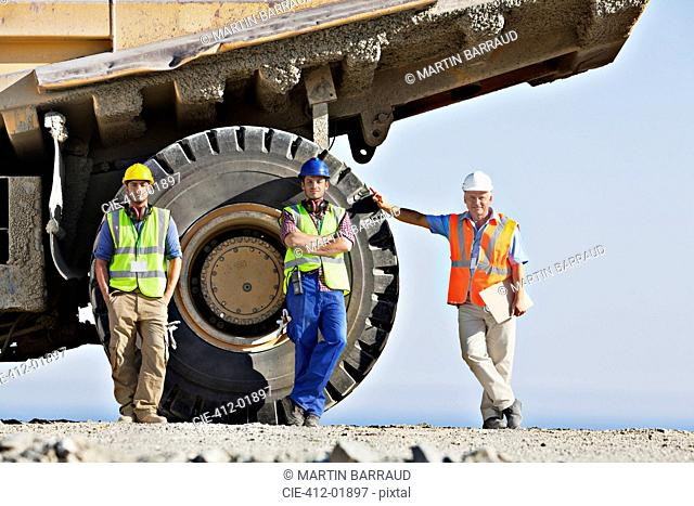 Workers standing by machinery on site