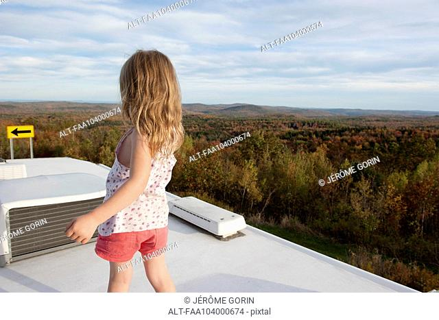 Little girl standing on top of motor home, looking at scenic view