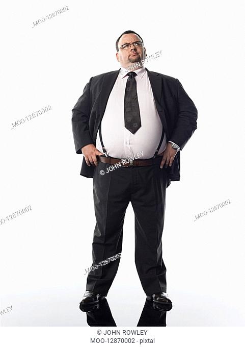 Overweight businessman standing with hands on hips