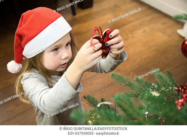 four years blonde cute girl with red Santa Claus hat, placing red heart and decorating Christmas tree at home