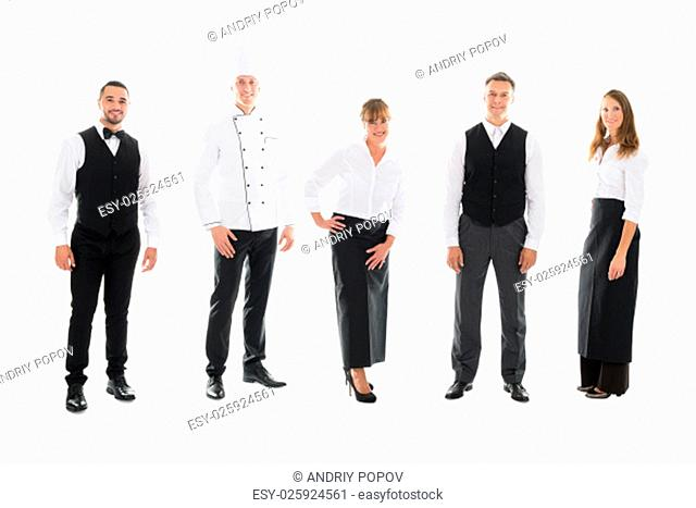 Full length portrait of happy restaurant staff standing over white background