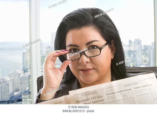 Hispanic businesswoman reading newspaper in office