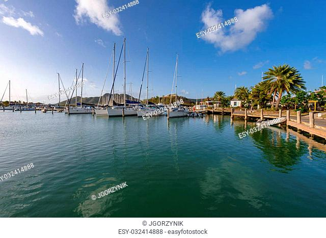 Yachts and power boats anchored in crystal clear turquoise waters in the Caribbean