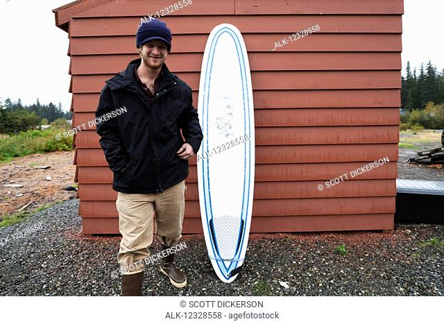 Young man standing next to a surfboard, South-central Alaska; Homer, Alaska, United States of America