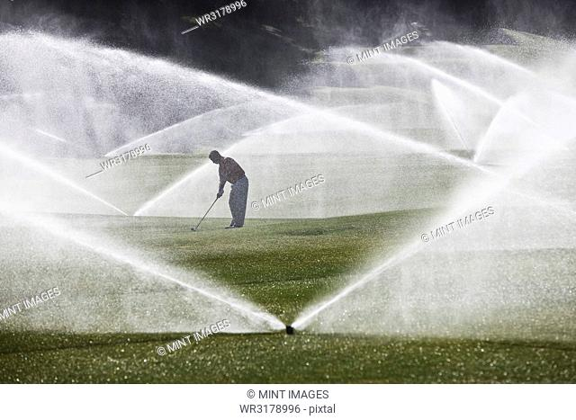 A golfer hitting his second shot on the fairway when the sprinkler system turns on