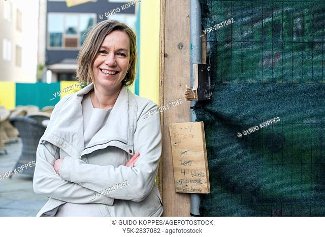 Zoetermeer, Netherlands. Portrait of a happy and smiling caucasian woman leaning against a construction site fence