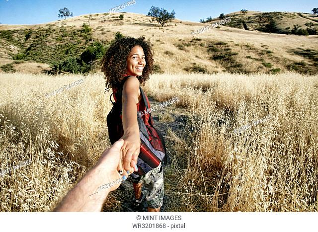 Young woman with curly brown hair hiking in urban park, holding man's hand