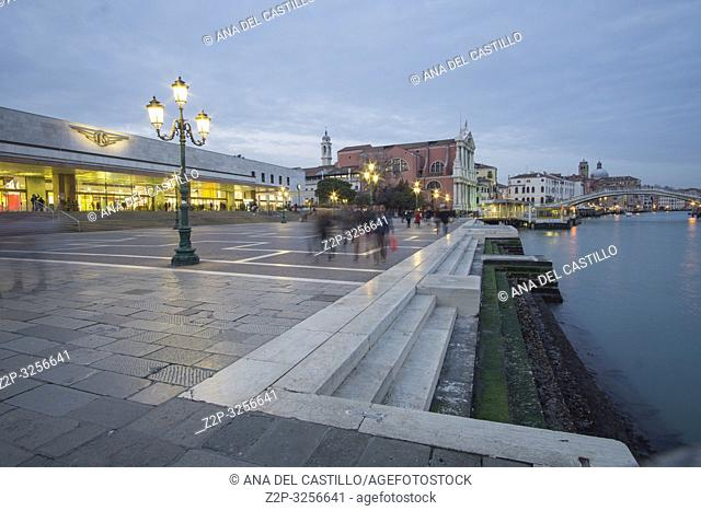 Venice, Veneto, Italy: Twilight in Grand Canal. Santa Lucia station with tourists departing and arriving