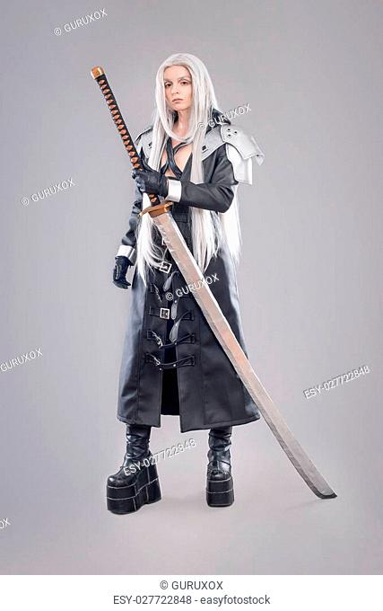 Woman warrior with sword and armor isolated on the gray background