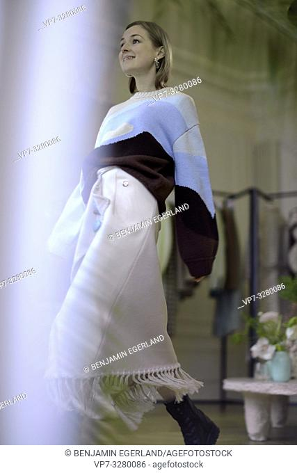 stylish woman trying new designer fashion collection in private showroom during fashion week, in Paris, France