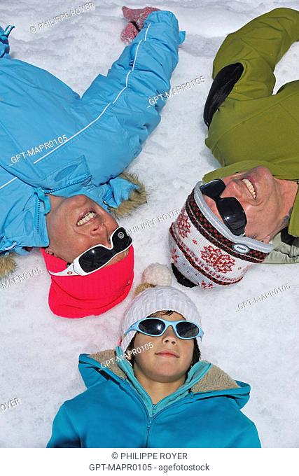 CHILD AND HIS PARENTS LYING IN THE SNOW, PORTRAIT OF A FAMILY ON A WINTER SPORTS VACATION, ALPS, SAVOY 73, RHONE-ALPES, FRANCE