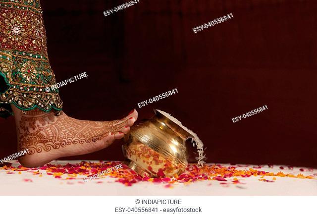 Brides foot kicking over a pot of rice