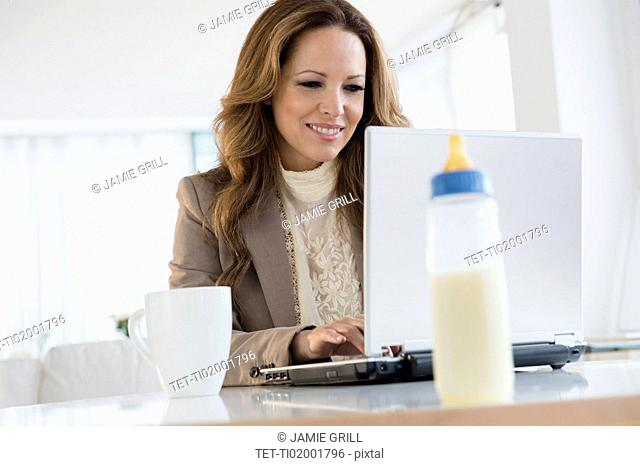 Portrait of working mother at laptop