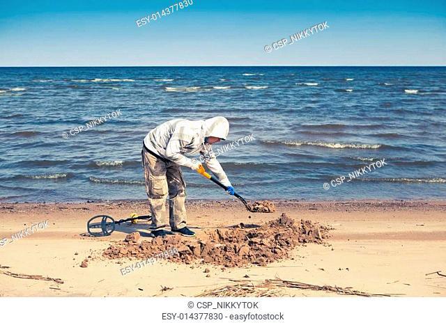 man digging a hole to pick up a treasure