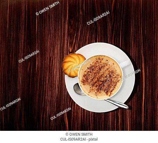 Overhead view of a cappuccino coffee on wooden table