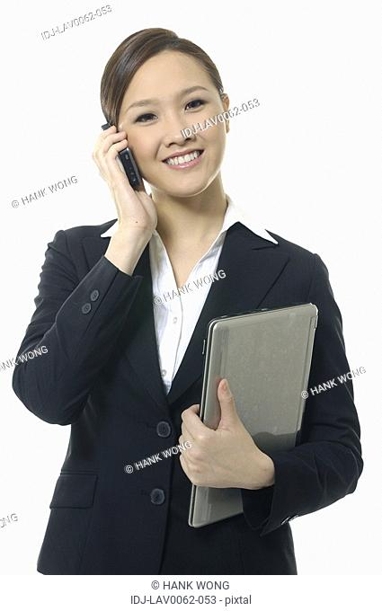 Portrait of a businesswoman holding a laptop and talking on a mobile phone