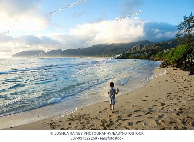 Lifestyle portrait of a young boy at sunrise on the beach in Oahu Hawaii while on vacation