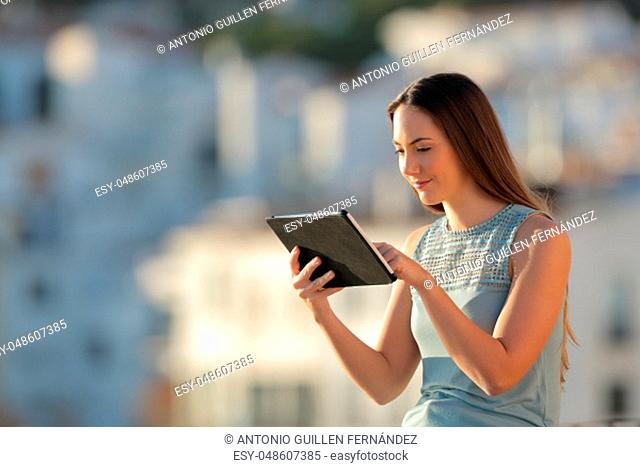 Serious woman uses a tablet in a town outskirts at sunset