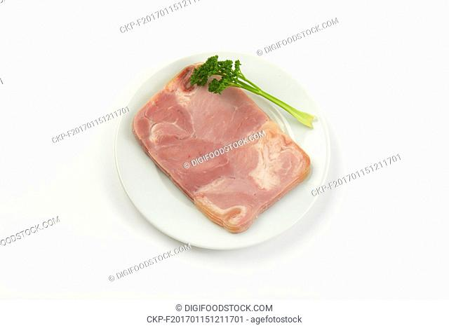 plate of fresh pork ham with parsley on white background