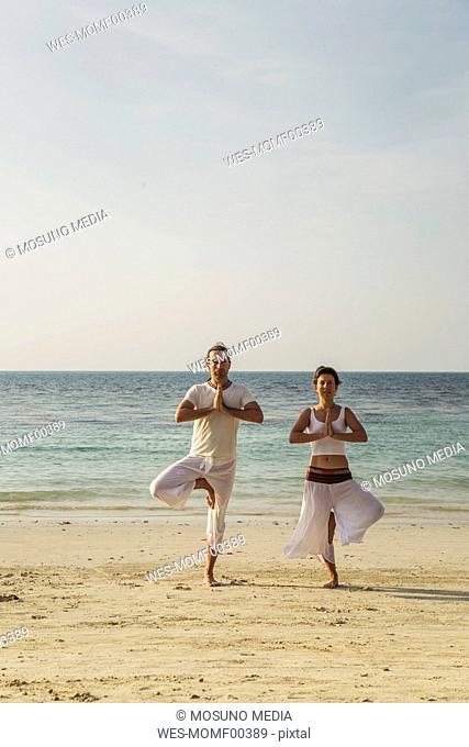 Thailand, Koh Phangan, couple doing yoga on a beach