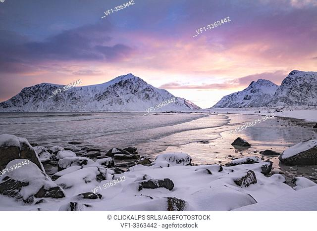 Skagsanden beach at dawn in winter, with rocks in the foreground. Flakstad, Nordland county, Northern Norway, Norway