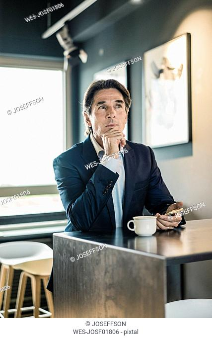 Businessman in cafeteria with cup of coffee thinking