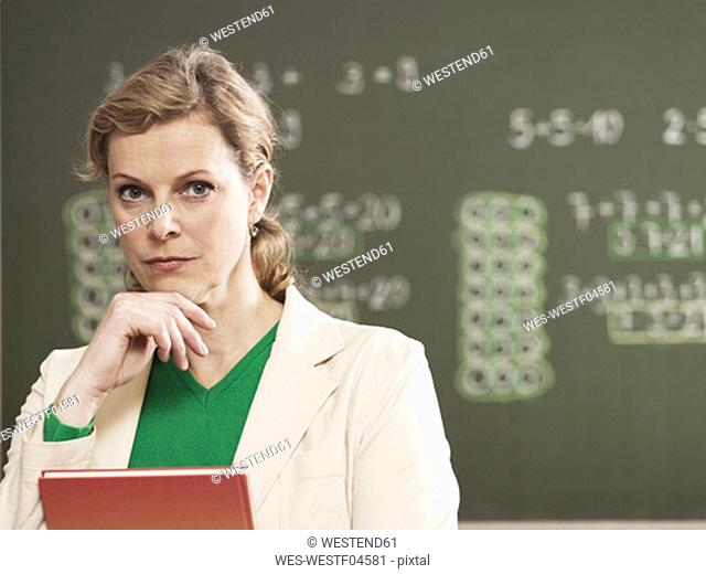 Woman holding documents, standing in front of blackboard