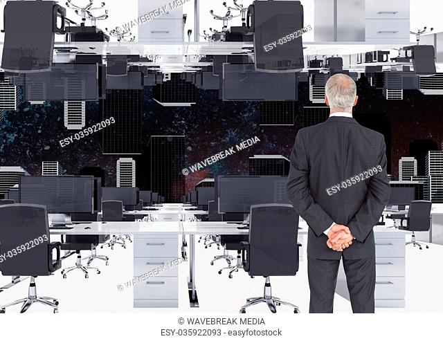 businessman standing in inverted office with skyline