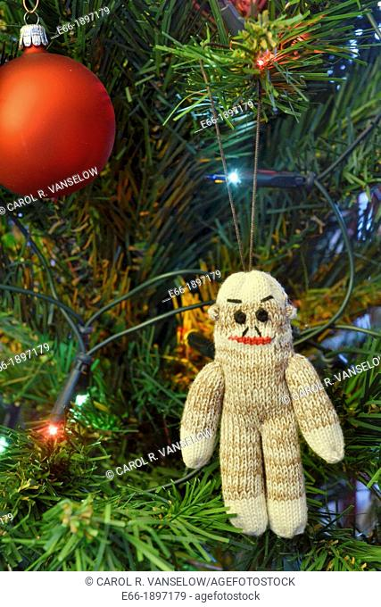 In addition to glass ball and lights, many people put handmade ornaments on their Christmas tree  Beige knit sock monkey