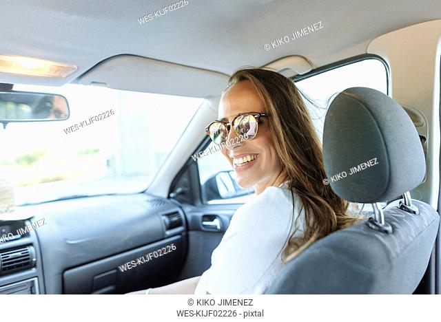 Happy woman on passenger seat in car