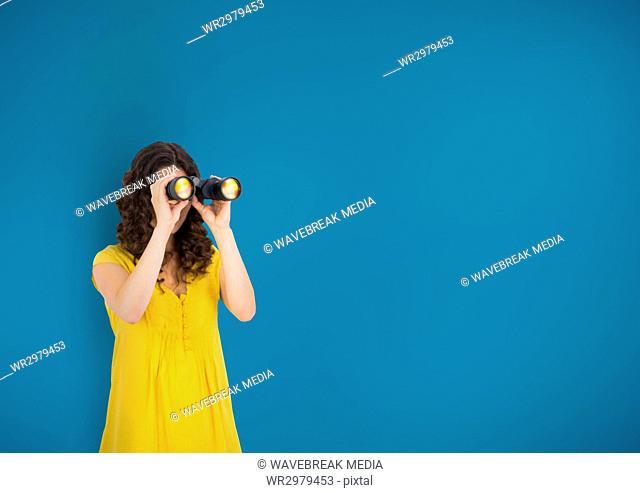 Woman looking through binoculars against blue background