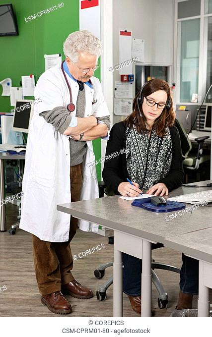 Assistant and doctor going over the list of appointments at a large medical clinic