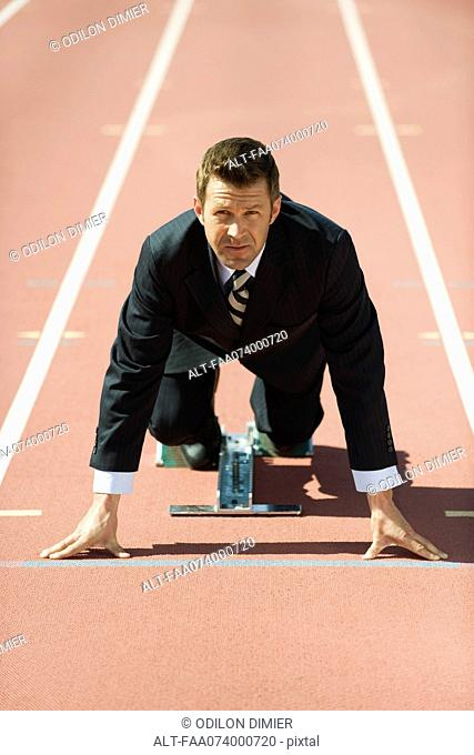 Businessman crouching at starting line on running track
