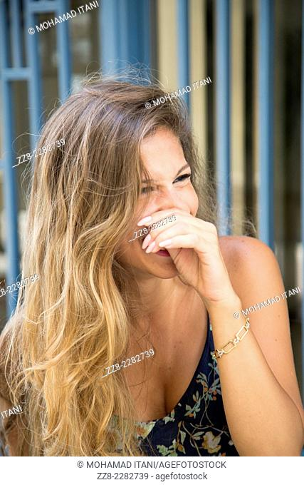 Happy young woman laughing outdoors while covering her mouth