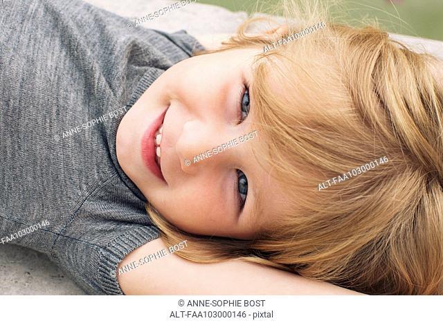 Little girl lying on her back, smiling, portrait