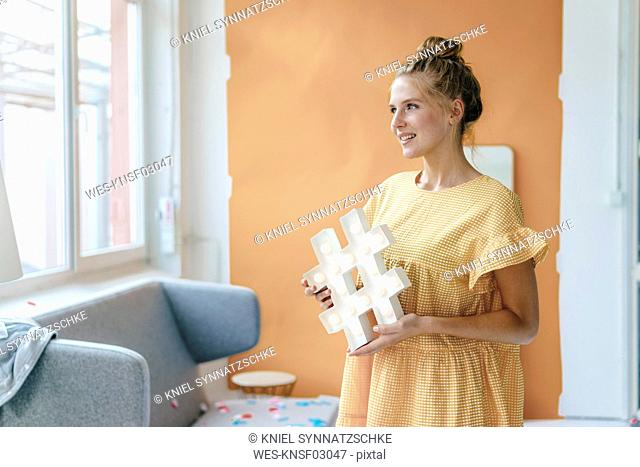 Smiling young woman holding hashtag sign