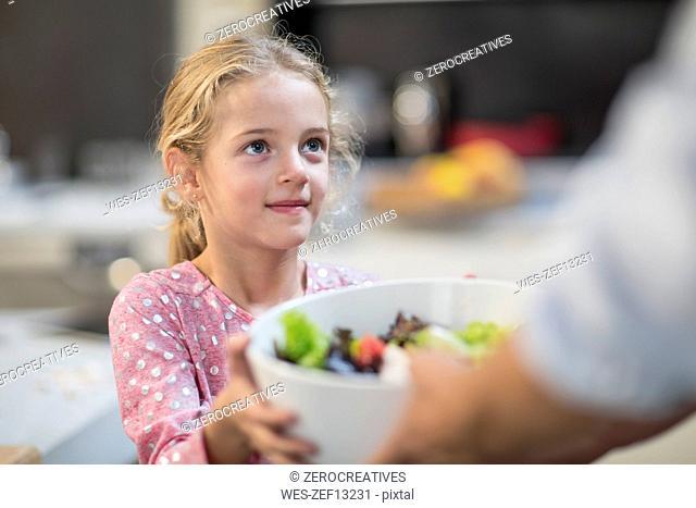 Girl receiving bowl of salad
