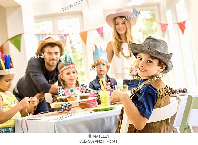 Portrait of parents and children at kids birthday party