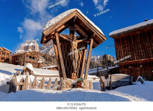 Wooden crucifix in the village of Coi. Winter in Zoldo Alto, Dolomites. In the background the wall of Pelmo mountain