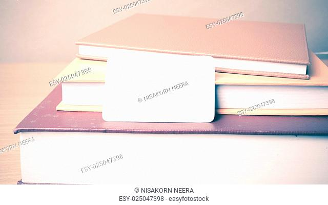 stack of book and business card on wood background vintage style