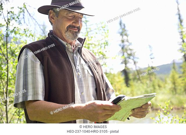 Senior man reading map in forest