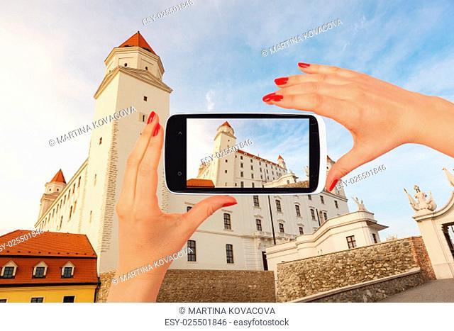 Bratislava castle tourism. Female tourist taking picture of Bratislava castle on smartphone. Tourism concept