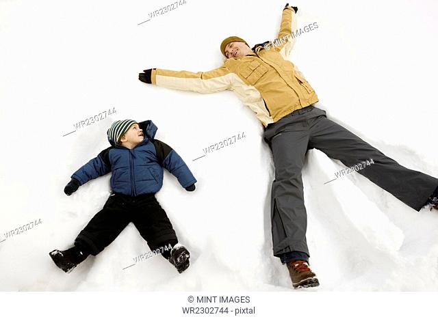 Two people, a man and a child lying in the snow make snow angel shapes