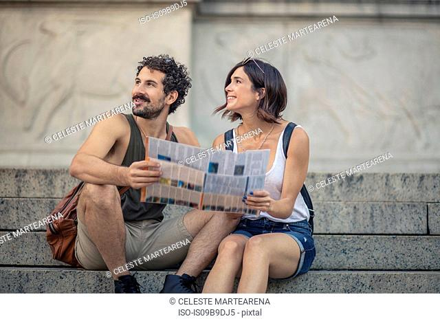 Happy tourist couple sitting on stairway with map looking up, Manhattan, New York, USA