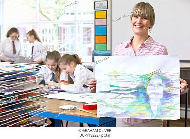 Portrait smiling art teacher showing painting in art class